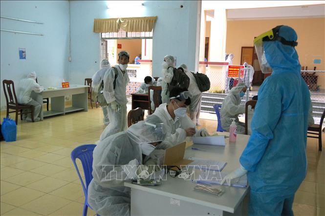 Các công dân kiểm tra y tế và làm thủ tục khai báo y tế tại buổi tiếp nhận tại Trường Quân sự tỉnh Sóc Trăng, sáng 13-10. Ảnh: Chanh Đa/TTXVN