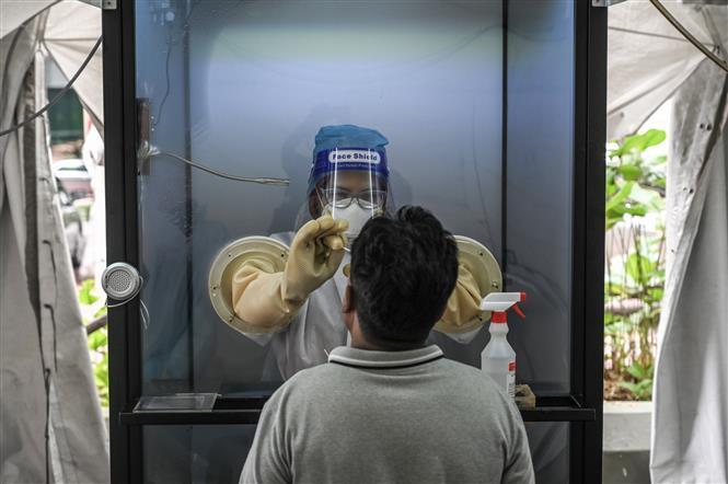 Nhân viên y tế lấy mẫu xét nghiệm COVID-19 tại Subang Jaya, ngoại ô Kuala Lumpur, Malaysia, ngày 22-10-2020. Ảnh: AFP/TTXVN