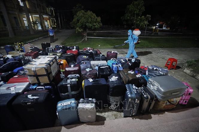 Toàn bộ hành lý của các công dân được phun hóa chất khử trùng khi chuyển về khu cách ly. Ảnh: Trọng Đạt/TTXVN