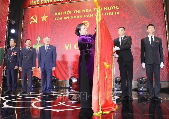 Chủ tịch Quốc hội Nguyễn Thị Kim Ngân gắn Huân chương Độc lập hạng Nhất lên lá cờ truyền thống của Tòa án nhân dân Tối cao. Ảnh. TTXVN