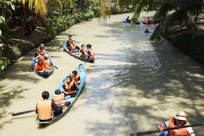 Du khách trải nghiệm chèo thuyền trên rạch tại một điểm du lịch ở TP. Bến Tre.