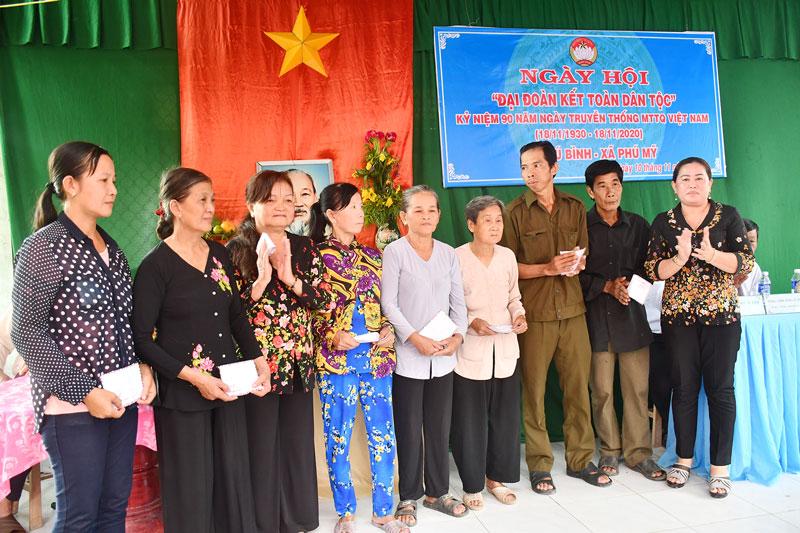 Phó bí thư Thường trực Huyện ủy Mỏ Cày Bắc Trần Thị Sol trao quà cho hộ nghèo ở xã Phú Mỹ.