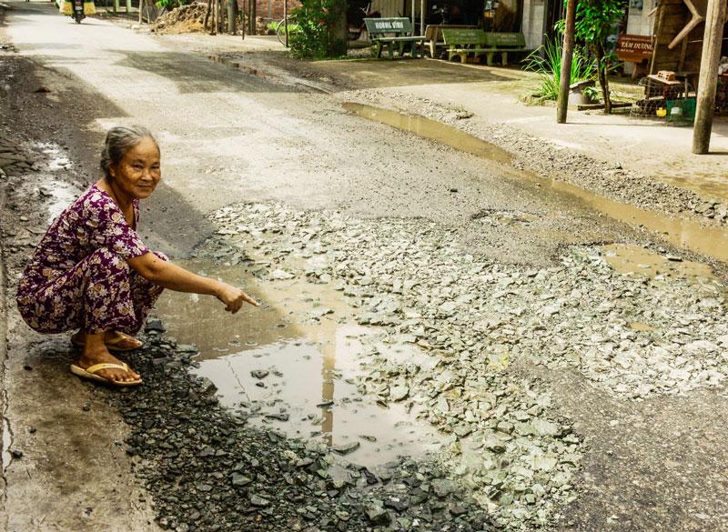 Bà Phan Thị Hồng chỉ chỗ lộ nhựa đã bị bong tróc.