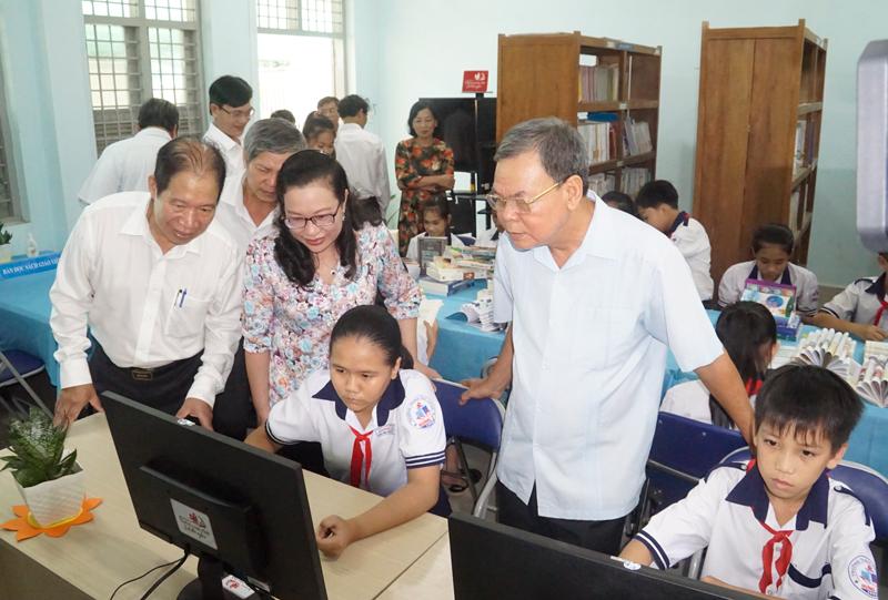Các đại biểu tham quan phòng lắp đặp máy tính và bàn đọc sách cho các em học sinh.