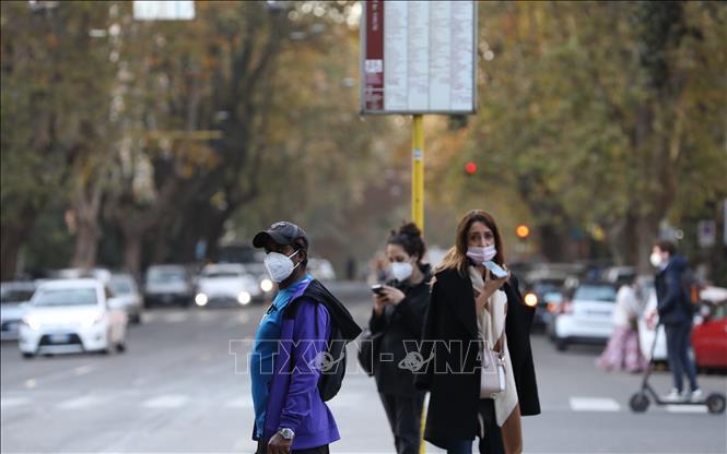 Người dân đeo khẩu trang đợi xe buýt ở Rome, Italy ngày 11-11-2020. Ảnh: THX/TTXVN