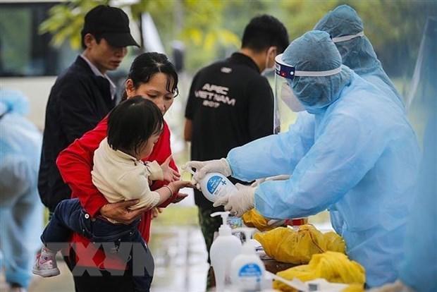 Các bác sĩ thực hiện sát khuẩn tay cho một cháu bé trong đoàn công dân cách ly tập trung theo dõi COVID-19 tại Trung đoàn 814, Bộ chỉ huy Quân sự tỉnh Hòa Bình. Ảnh minh họa: TTXVN