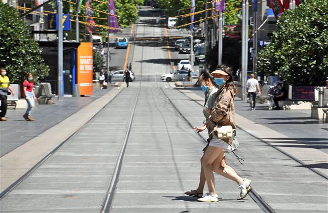 Người dân đeo khẩu trang phòng dịch COVID-19 khi di chuyển trên phố ở Melbourne, bang Victoria, Australia ngày 9-11-2020. Ảnh: AFP/TTXVN