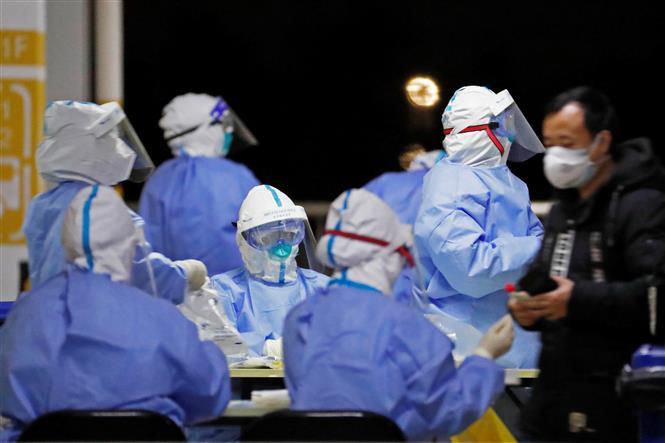 Nhân viên y tế xét nghiệm COVID-19 cho nhân viên sân bay quốc tế Phố Đông ở Thượng Hải, Trung Quốc, ngày 22-11-2020. Ảnh: AFP/ TTXVN