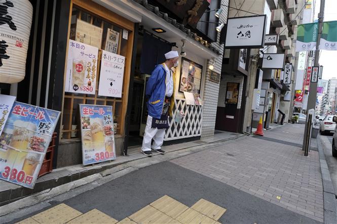 Nhân viên đợi đón khách tại một nhà hàng tại Tokyo, Nhật Bản, ngày 15-4-2020. Ảnh: AFP/ TTXVN