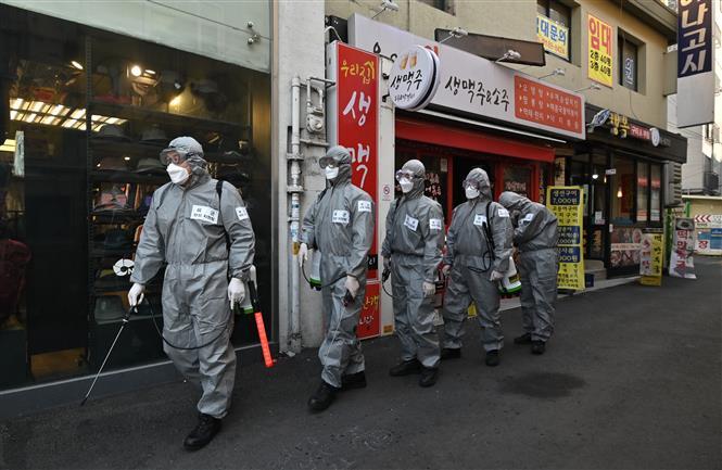 Binh sĩ Hàn Quốc phun thuốc khử trùng nhằm ngăn dịch COVID-19 lây lan tại Seoul. Ảnh: AFP/TTXVN