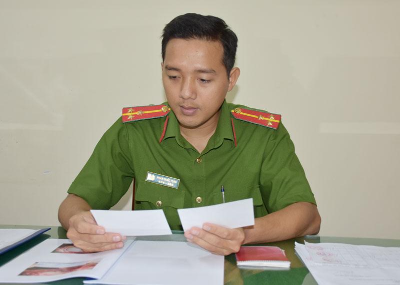 Thượng úy Phạm Quốc Toản xem lại bản ảnh pháp y.
