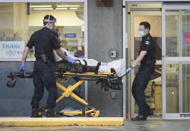 Nhân viên y tế chuyển bệnh nhân COVID-19 tới bệnh viện tại Vancouver, British Columbia, Canada, ngày 24-11-2020. Ảnh: THX/ TTXVN