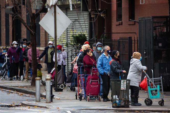 Người dân đeo khẩu trang phòng lây nhiễm COVID-19 khi xếp hàng bên ngoài một cửa hàng thực phẩm ở Brooklyn, New York, Mỹ, ngày 12-11-2020. Ảnh: THX/ TTXVN