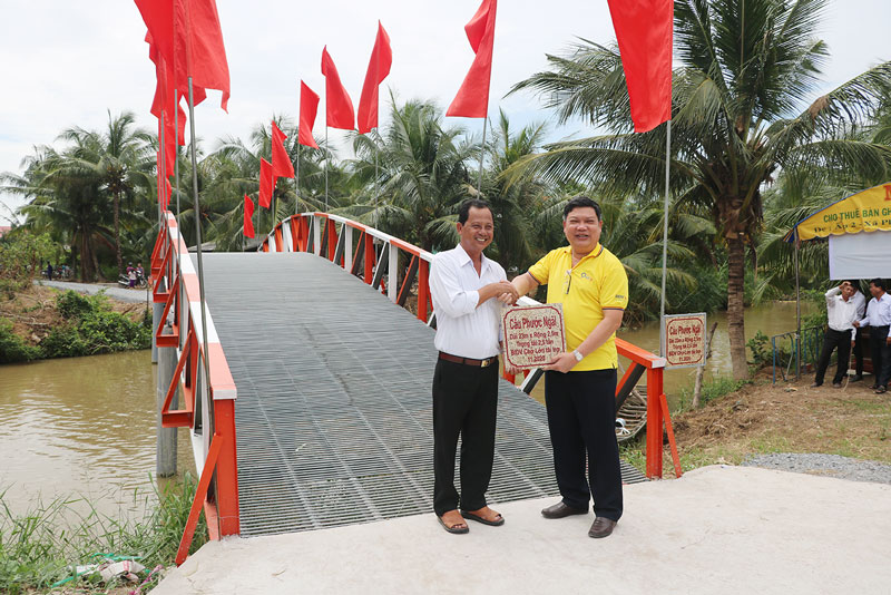 Ông Nguyễn Thế Kế - Giám đốc BIDV Chi nhánh Chợ Lớn (bên phải) trao bảng tặng cầu cho lãnh đạo xã Phước Ngãi. Ảnh: T. Thảo