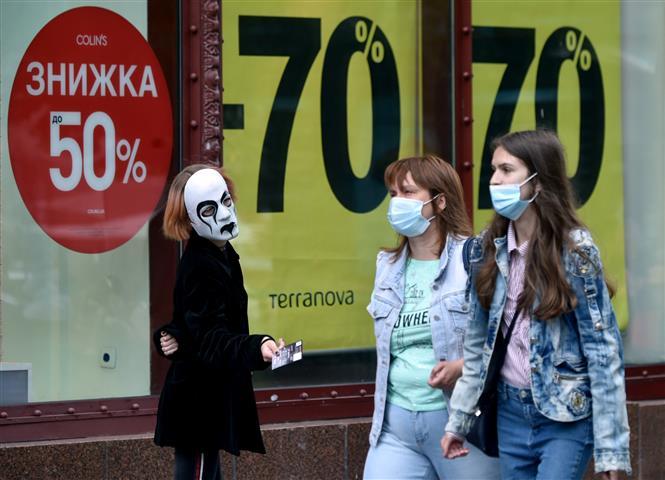 Người dân đeo khẩu trang nhằm ngăn dịch COVID-19 lây lan tại Kiev, Ukraine. Ảnh: AFP/TTXVN