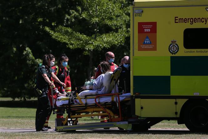Nhân viên y tế chuyển bệnh nhân mắc COVID-19 lên xe cứu thương tại London, Anh ngày 20-5-2020. Ảnh: AFP/TTXVN
