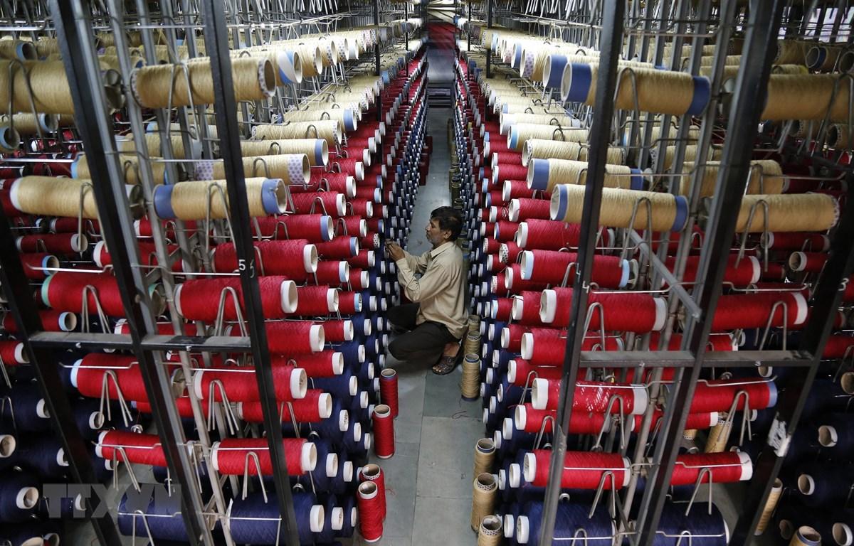 Công nhân kiểm tra các ống sợi trên máy dệt thảm tại một nhà máy ở ngoại ô Jammu, Ấn Độ. Ảnh: AFP/TTXVN