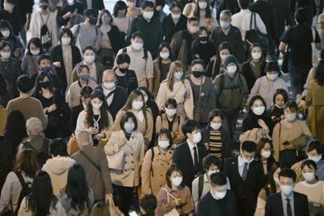 Người dân đeo khẩu trang phòng dịch COVID-19 khi lưu thông trên đường phố ở Osaka, Nhật Bản ngày 20-11-2020. Ảnh: Kyodo/TTXVN