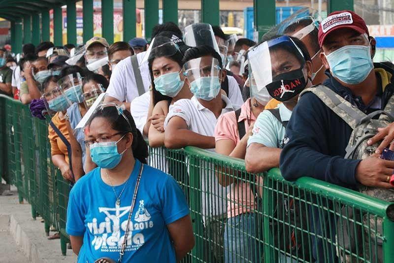 Người dân đeo khẩu trang chờ xe buýt ở Philippines ngày 1-10-2020. Ảnh: The Star