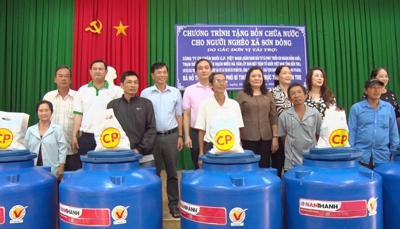 Phó bí thư Thường trực Tỉnh ủy Hồ Thị Hoàng Yến và các mạnh thường quân trao bồn nước, quà cho người dân.