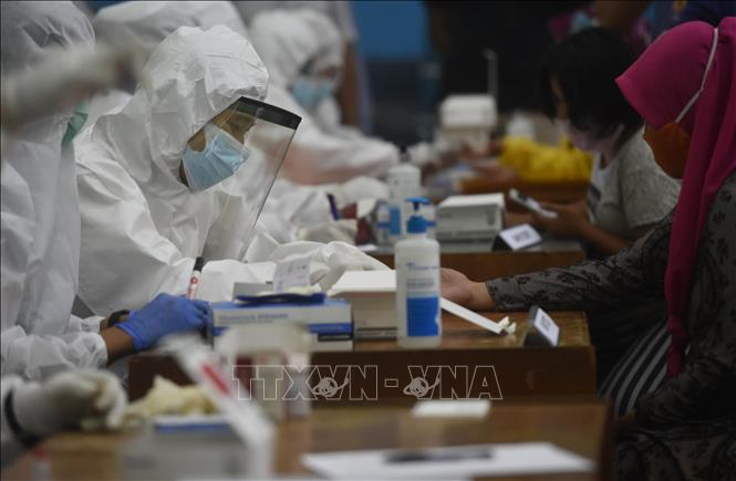Nhân viên y tế lấy mẫu xét nghiệm COVID-19 cho người dân tại Jakarta, Indonesia. Ảnh: THX/TTXVN