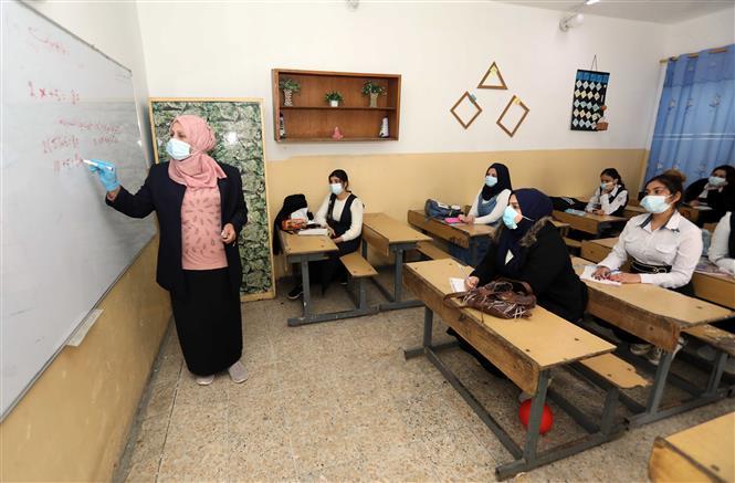 Giáo viên và học sinh đeo khẩu trang phòng lây nhiễm COVID-19 tại trường học ở Baghdad, Iraq, ngày 29-11-2020. Ảnh: THX/TTXVN