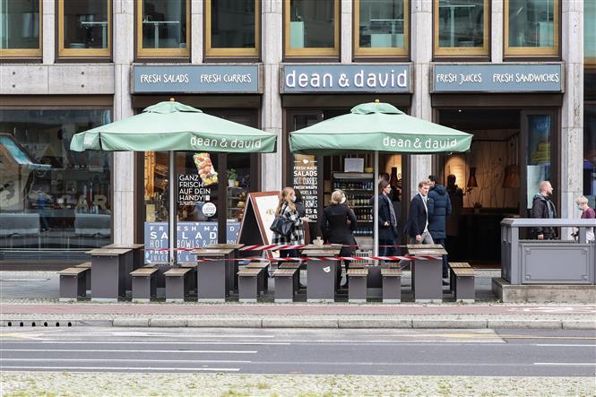 Khách hàng chờ mua đồ mang đi bên ngoài một nhà hàng ở Berlin, Đức trong bối cảnh lệnh hạn chế được áp đặt nhằm ngăn dịch COVID-19 lây lan, ngày 2-11-20202. Ảnh: THX/TTXVN