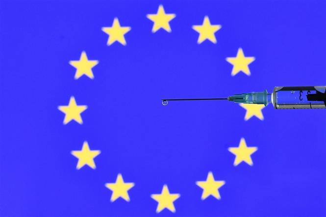 Biểu tượng tiêm phòng vắc-xin COVID-19 trên nền cờ Liên minh châu Âu, ngày 17-11-2020. Ảnh: AFP/TTXVN