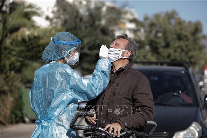 Nhân viên y tế lấy mẫu xét nghiệm COVID-19 cho người dân tại Glyfada, phía nam thủ đô Athens, Hy Lạp, ngày 28-11. Ảnh: THX/TTXVN