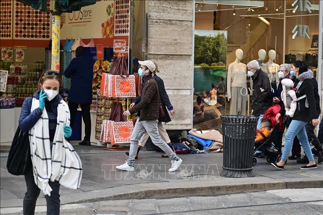 Người dân di chuyển trên đường phố tại Milan, Italy, ngày 20-10. Ảnh: AFP/TTXVN