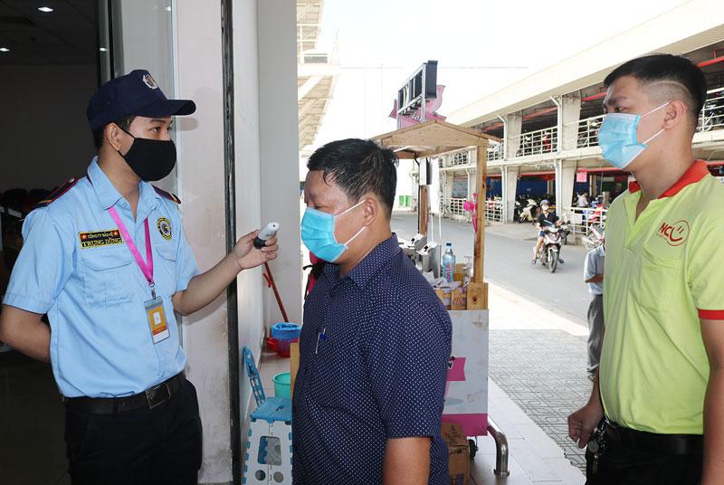 Nhân viên siêu thị Co.opMart Bến Tre đo thân nhiệt và nhắc khách hàng đeo khẩu trang để phòng chống dịch Covid-19.