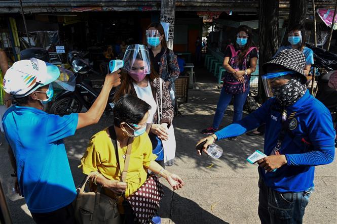 Kiểm tra thân nhiệt cho hành khách trước khi lên xe buýt tại Manila, Philippines. Ảnh: AFP/TTXVN