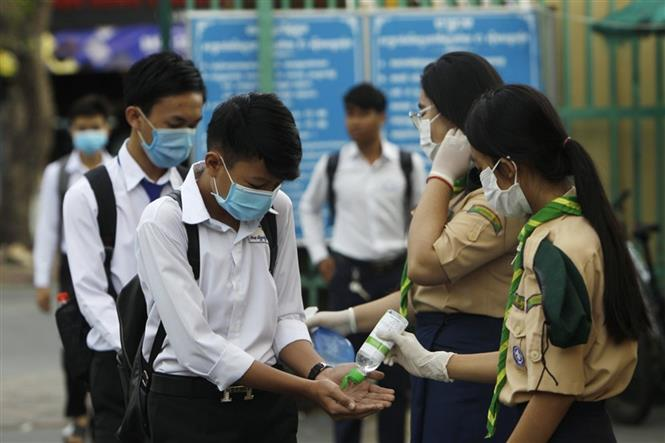 Các học sinh tiến hành sát khuẩn tay nhằm ngăn dịch COVID-19 lây lan, trước khi vào lớp ở Phnom Penh, Campuchia, ngày 2-11-2020. Ảnh: AFP/TTXVN