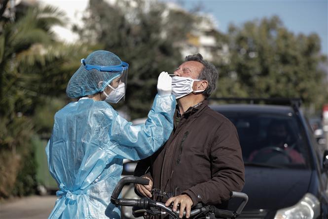 Nhân viên y tế lấy mẫu xét nghiệm COVID-19 cho người dân tại Glyfada, Hy Lạp ngày 28-11-2020. Ảnh: THX/TTXVN