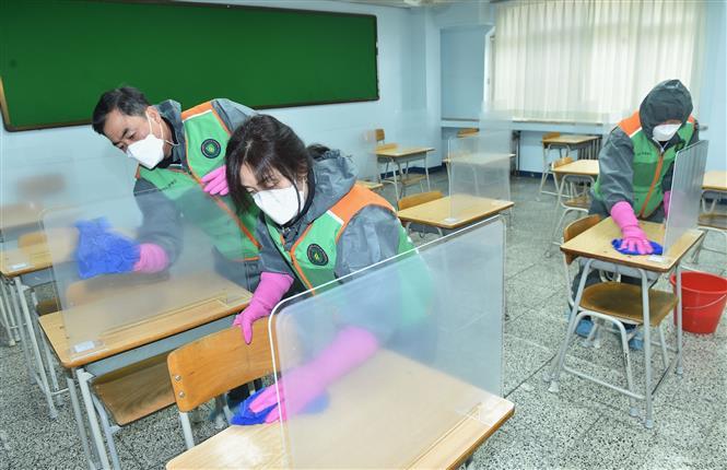 Nhân viên dọn vệ sinh nhằm ngăn chặn sự lây lan của dịch COVID-19 tại phòng thi của một trường trung học ở Seongnam, Hàn Quốc ngày 2-12-2020.