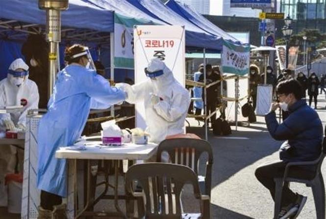 Nhân viên y tế lấy mẫu xét nghiệm COVID-19 cho người dân tại Seoul, Hàn Quốc ngày 14-12-2020. Ảnh: Kyodo/TTXVN