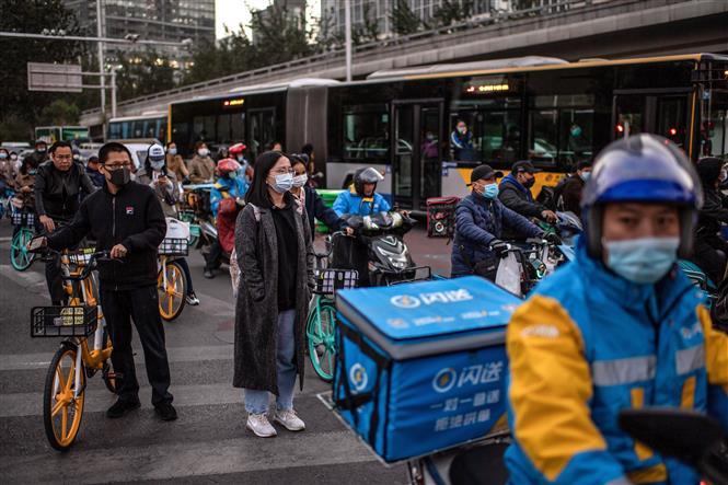 Người dân đeo khẩu trang phòng lây nhiễm COVID-19 tại Bắc Kinh, Trung Quốc, ngày 21-10-2020. Ảnh: AFP/ TTXVN