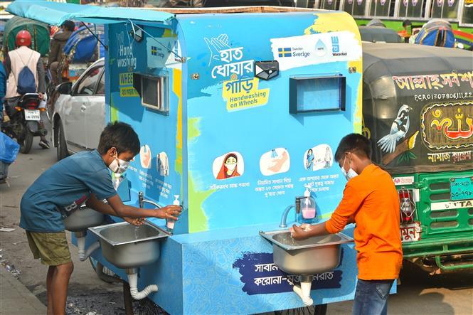 Trẻ em rửa tay phòng lây nhiễm COVID-19 tại trạm rửa tay di động ở Dhaka, Bangladesh, ngày 21-12-2020. Ảnh: THX/ TTXVN