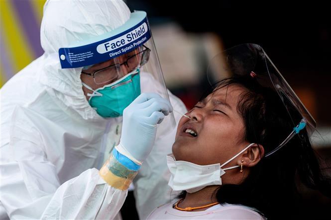 Nhân viên y tế lấy mẫu xét nghiệm COVID-19 cho người dân tại Samut Sakhon, Thái Lan, ngày 19-12-2020. Ảnh: AFP/TTXVN