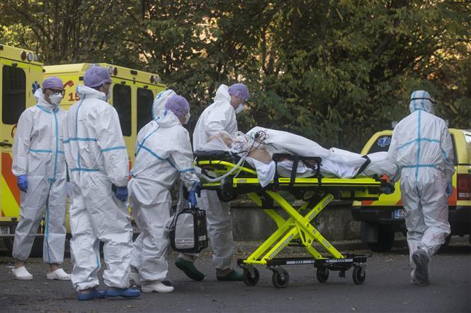 Nhân viên y tế chuyển bệnh nhân COVID-19 tới bệnh viện ở Praha, CH Séc. Ảnh: AFP/ TTXVN