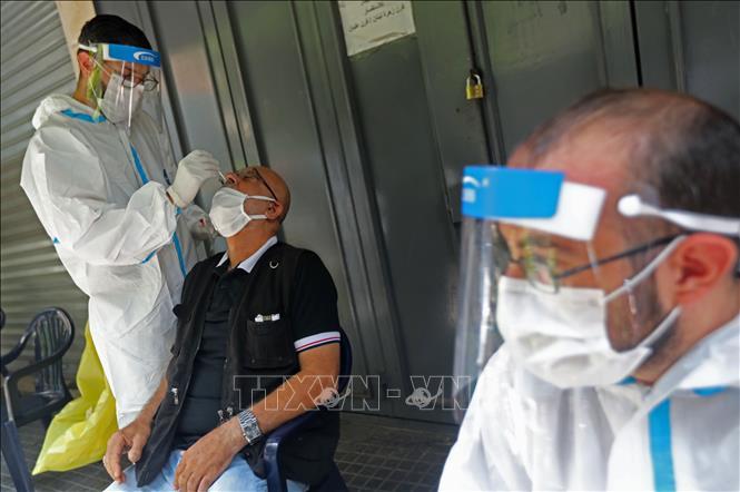 Nhân viên y tế lấy mẫu xét nghiệm COVID-19 tại Beirut, Liban. Ảnh: THX/TTXVN