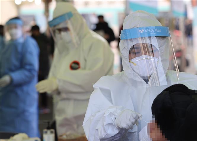Nhân viên y tế lấy mẫu xét nghiệm COVID-19 cho người dân tại trung tâm xét nghiệm tạm thời ở ngoại ô Seoul, Hàn Quốc ngày 26-12-2020. Ảnh: YONHAP/TTXVN
