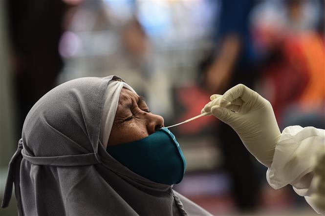 Nhân viên y tế lấy mẫu xét nghiệm COVID-19 cho người dân tại Jakarta, Indonesia ngày 22-12-2020. Ảnh: THX/TTXVN