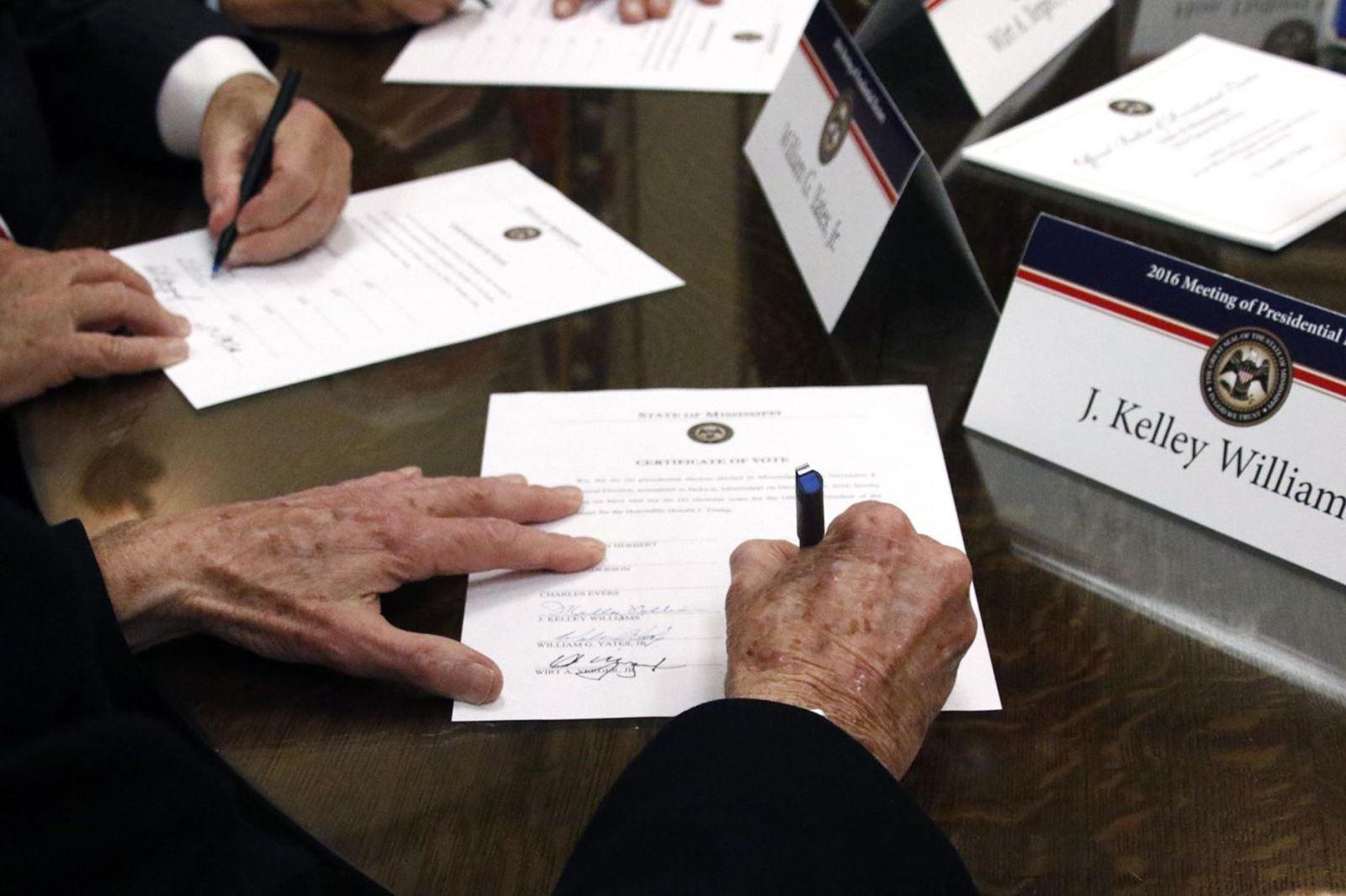 Cử tri đoàn ký xác nhận lá phiếu bầu Tổng thống và Phó Tổng thống Mỹ tại phiên bỏ phiếu của các đại cử tri ở Lansing, bang Michigan ngày 14-12. Ảnh: AFP/TTXVN