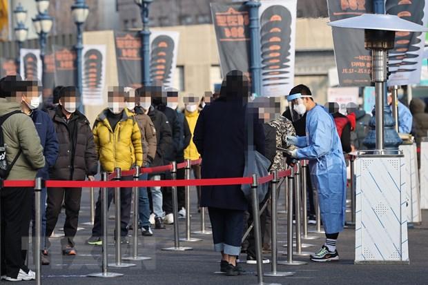 Nhân viên y tế lấy mẫu xét nghiệm COVID-19 cho người dân tại trung tâm xét nghiệm tạm thời ở ngoại ô Seoul, Hàn Quốc ngày 26-12-2020. (Ảnh: YONHAP/TTXVN)