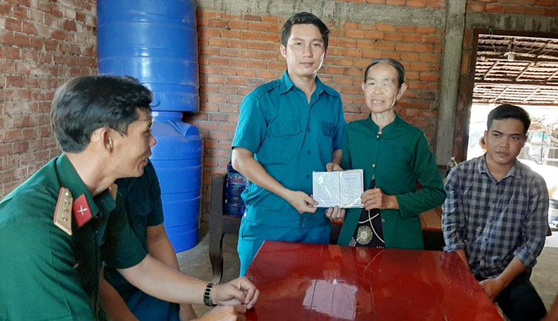Cán bộ Ban Chỉ huy Quân sự xã An Hòa Tây (Ba Tri) tặng sổ tiết kiệm cho thanh niên chuẩn bị lên đường nhập ngũ. Ảnh: Đặng Thạch