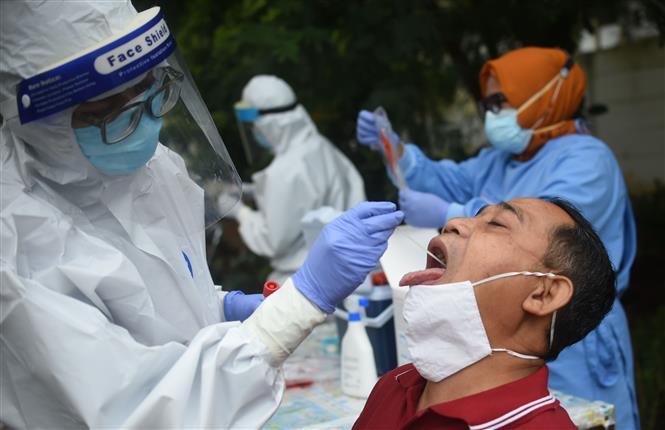 Nhân viên y tế lấy mẫu xét nghiệm COVID-19 cho người dân Indonesia ngày 7-1-2021. Ảnh: THX/ TTXVN  Indonesia: Nguy cơ không đủ ngân sách để giải cứu nền kinh tế