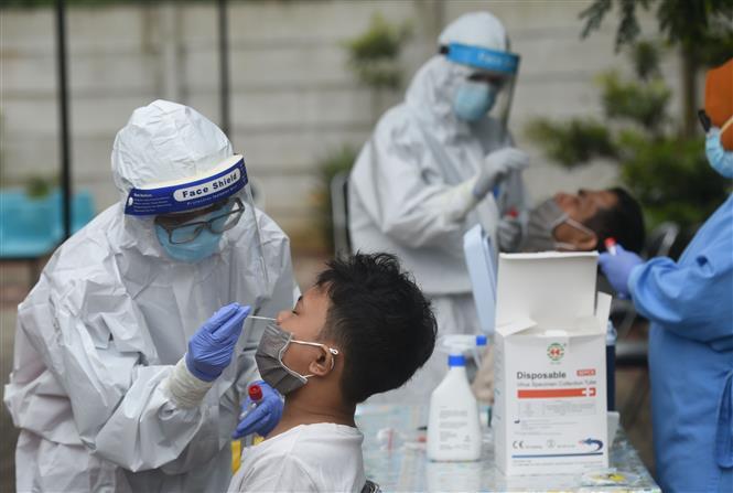 Nhân viên y tế lấy mẫu dịch xét nghiệm COVID-19 cho trẻ em tại Jakarta, Indonesia, ngày 7-1-2021. Ảnh: THX/ TTXVN