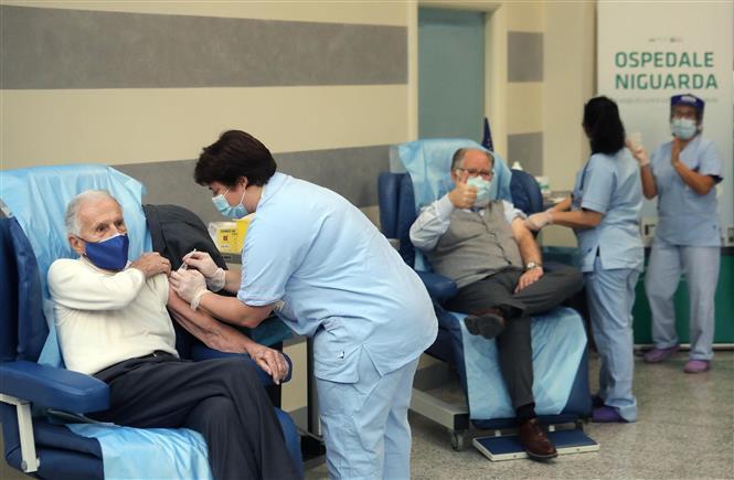 Nhân viên y tế tiêm chủng vaccine ngừa COVID-19 cho người dân tại Milan, Italy, ngày 27-12-2020. Ảnh: AFP/TTXVN