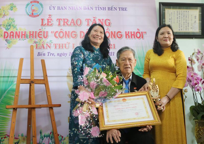 Phó Bí thư Thường trực Tỉnh ủy Hồ Thị Hoàng Yến (bìa phải), Phó Chủ tịch UBND tỉnh Nguyễn Thị Bé Mười (bìa trái) trao hoa và danh hiệu cho ông Huỳnh Văn Cam.